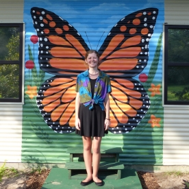 Arianna, standing in front of the butterfly mural painted by Emily Strickland.