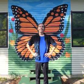 Avery, standing in front of the butterfly mural painted by Emily Strickland.
