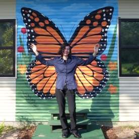 Kai, standing in front of the butterfly mural painted by Emily Strickland.